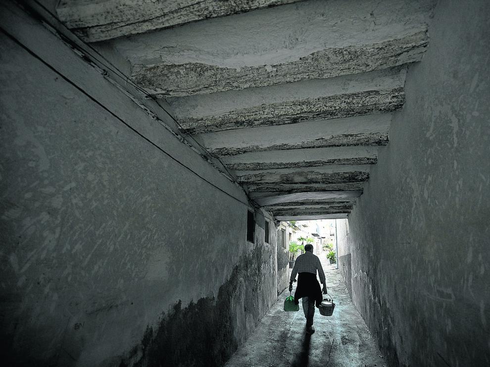 Un vecino de Sabiñán, cargado con dos cubos, camina por el florido callejón que conduce a su residencia.