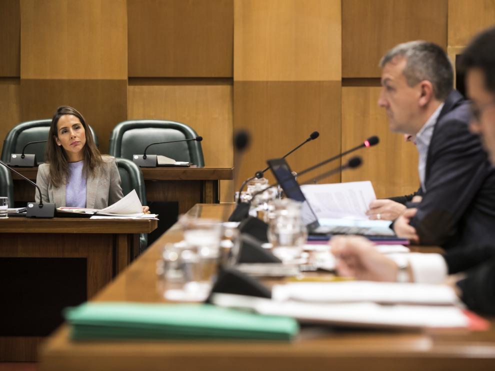 La edil del PP María Navarro, a la izquierda, durante una de las intervenciones de este viernes del concejal de Economía, Fernando Rivarés.
