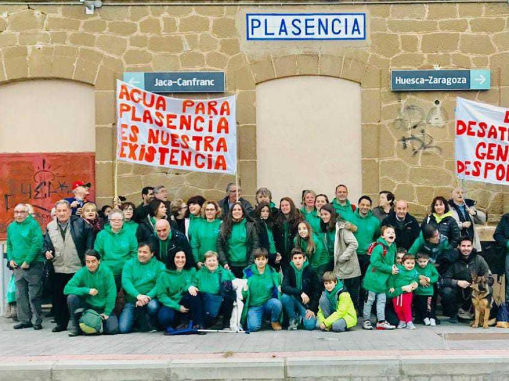 Foto de familia de los vecinos con las pancartas de protesta en el apeadero de Plasencia del Monte