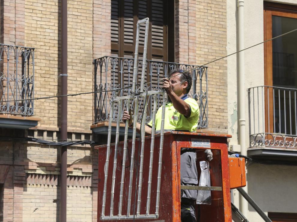 Un operario de las brigadas municipales coloca la iluminación de las Fiestas de San Lorenzo