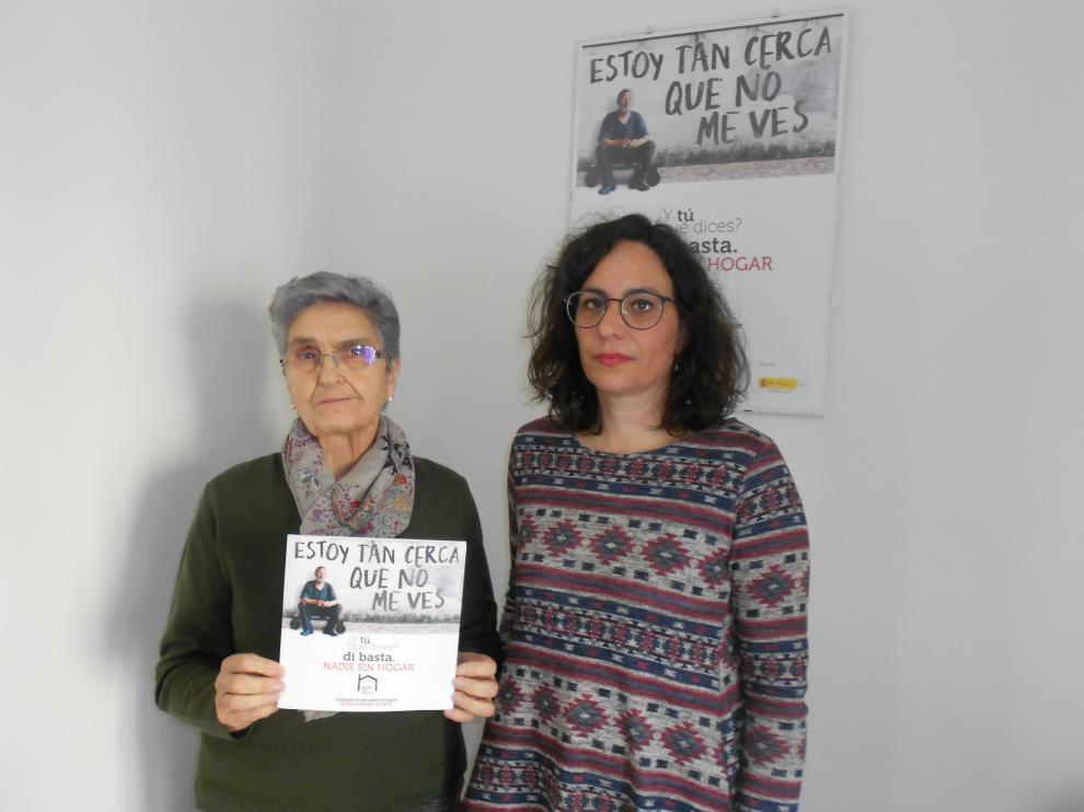 Raquel Mayayo (izq.) y Gema López (der.) de Cáritas Tarazona posan con el tríptico de la campaña.