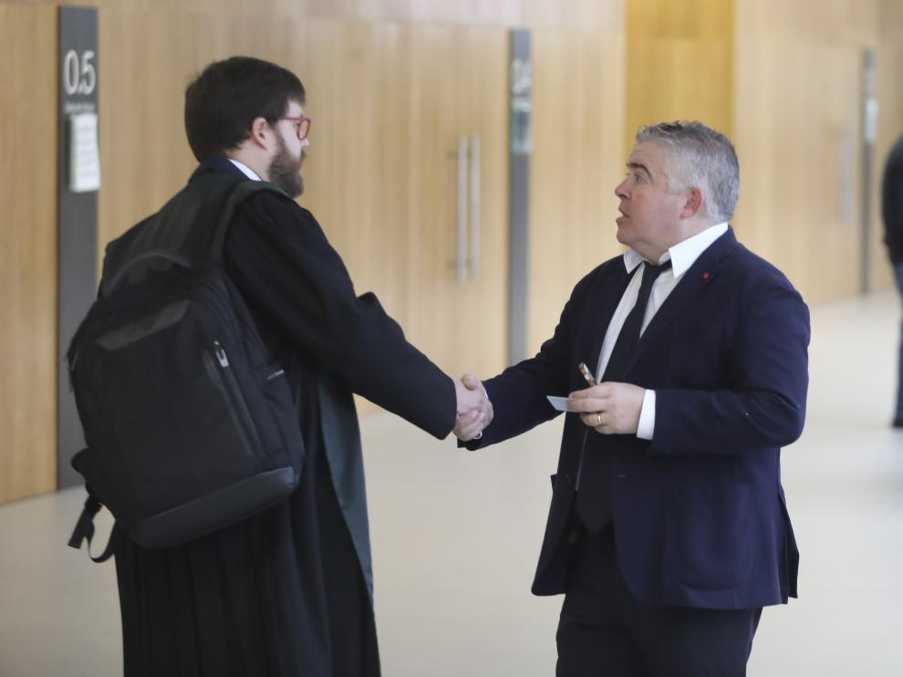 El abogado Javier Vilarrubí, a la derecha, estrecha la mano de otro de los letrados del caso tras cerrar un acuerdo entre todas las partes