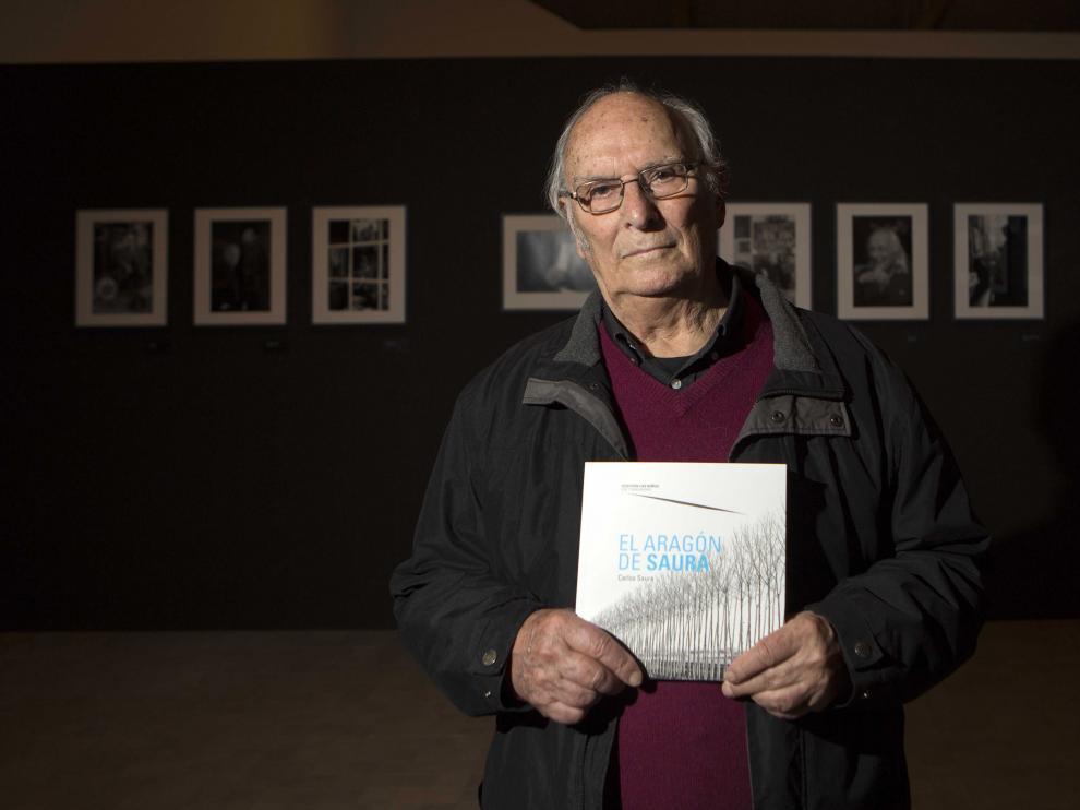 Carlos Saura con el libro de fotografías y paisajes pintados de Aragón.