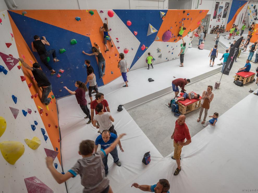 Niños y adultos practicando boulder en las instalaciones del centro Bulderland de Zaragoza.