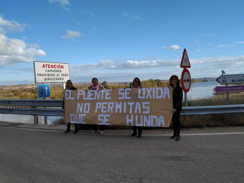 Reyes, Mari Carmen, María José y Tere, madres de alumnos, con una pancarta en el puente.