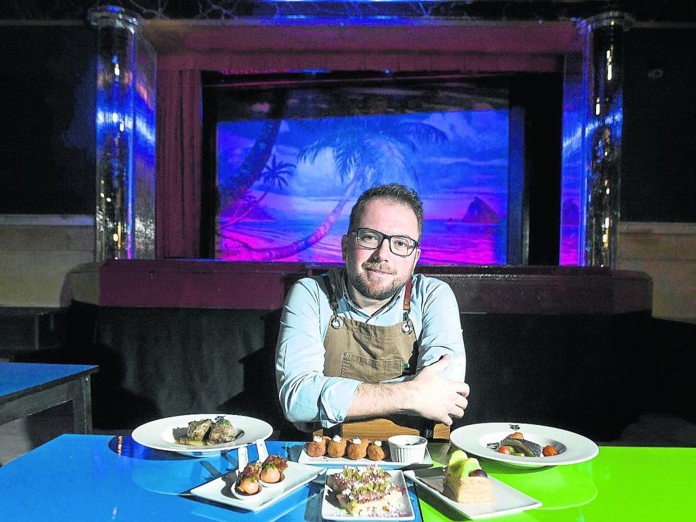 Alberto Brosed, apoyado en las singulares mesas del Café El Plata y su escenario al fonda, posa con sus recetas.