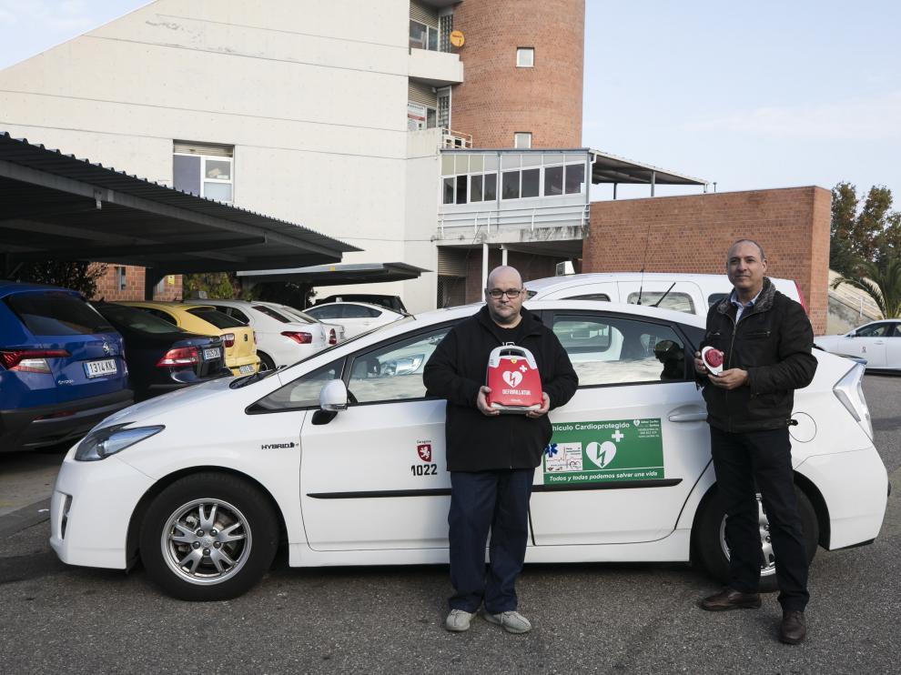 Javier Burgos, a la izquierda, y Ángel Hernández, muestran el desfibrilador instalado en el taxi 'cardioprotegido'.