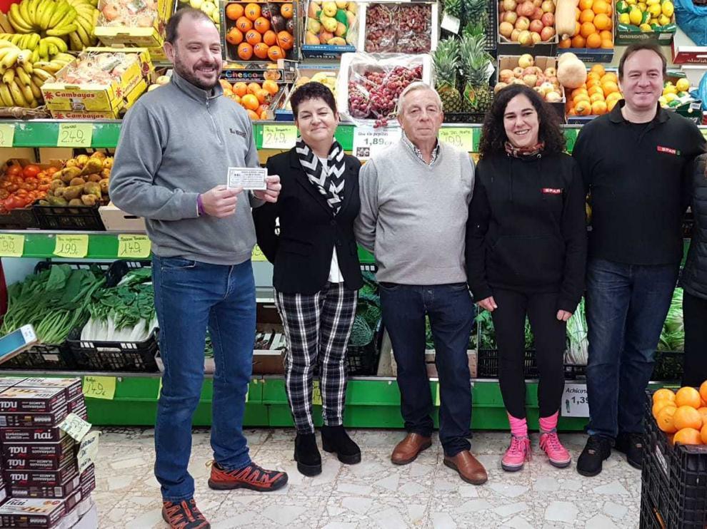 Óscar Aguado, primero por la izquierda, con el boleto ganador de los 6.000 euros en compras de la ACT en la tienda de alimentación que ha repartido el premio.