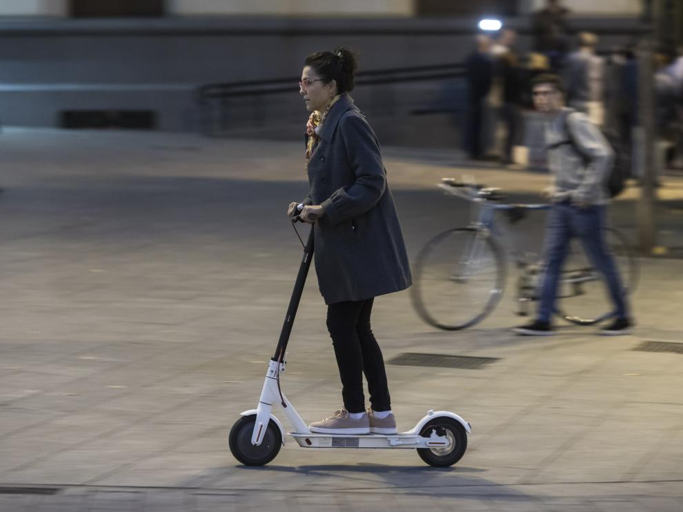 Un usuario de un patinete eléctrico, circulando por una acera.