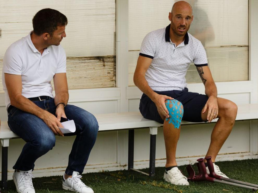Toquero, con las muletas, junto a Lalo Arantegui a finales de julio en el amistoso de pretemporada que el Real Zaragoza jugó en Tudela. Fue su primera aparición pública desde la campaña anterior.