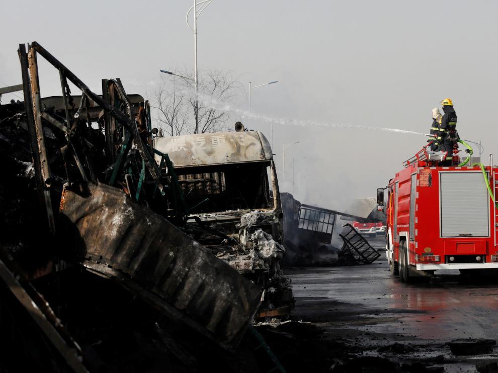 Bomberos apagando el fuego de uno de los camiones incendiados.