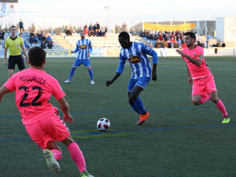 El jugador del Ejea, Moustapha, conduce el balón ante la presión de varios rivales del CD Castellón.