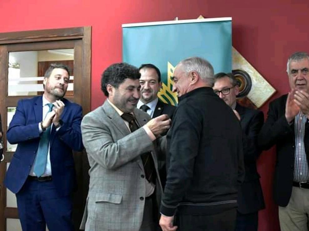 Miguel Tomás recibe la medalla de Juan Carlos Escuder, presidente de los empresarios de Gúdar-Javalambre, en Mora de Rubielos.