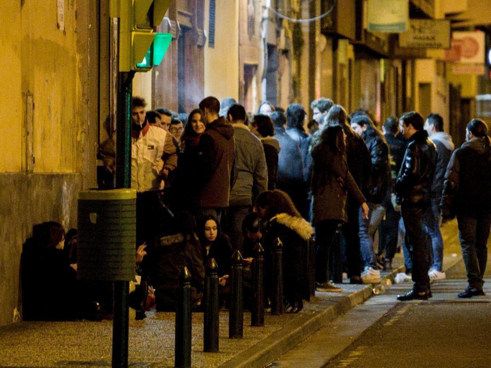 Un grupo de jóvenes consume alcohol a las puertas de un bar en la zona del Rollo.