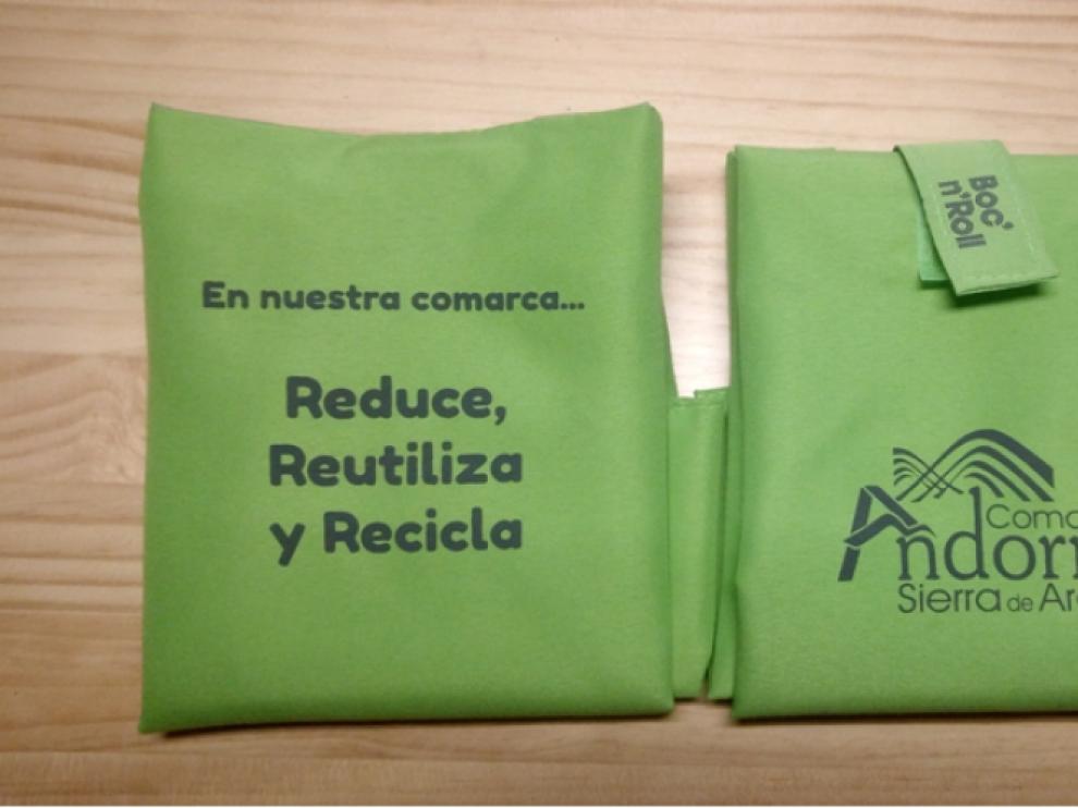 El portabocadillos es verde y lleva el logo de la comarca y un eslogan.
