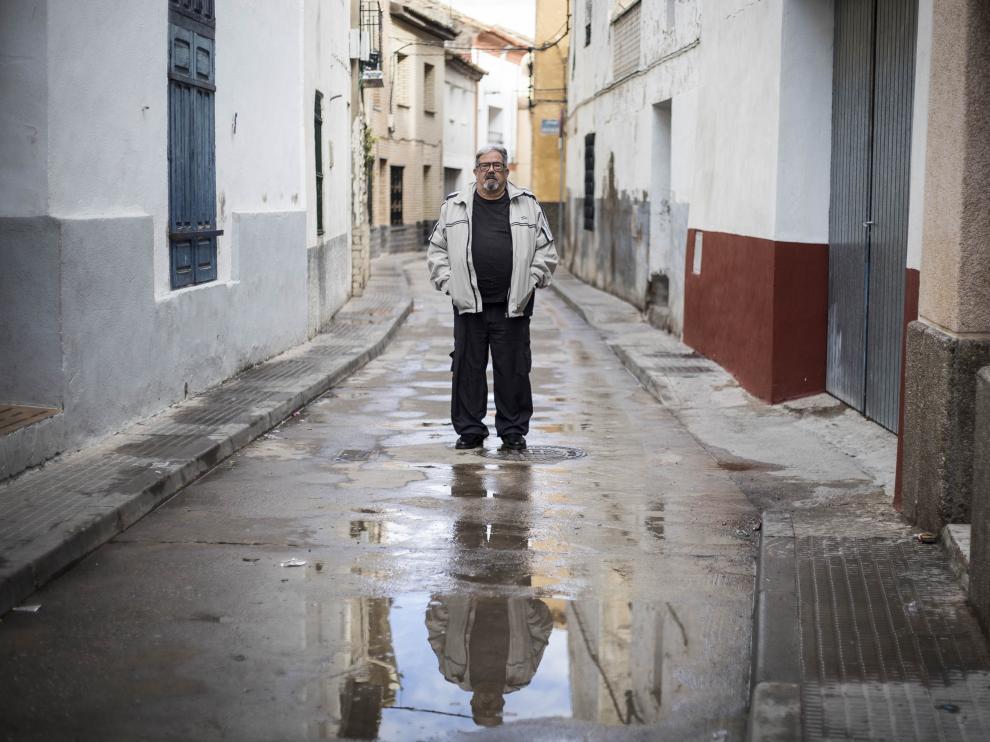 El cocinero y escritor local Jesús Aznar (con su reflejo en el agua) posa en una estrecha calle de Lumpiaque.