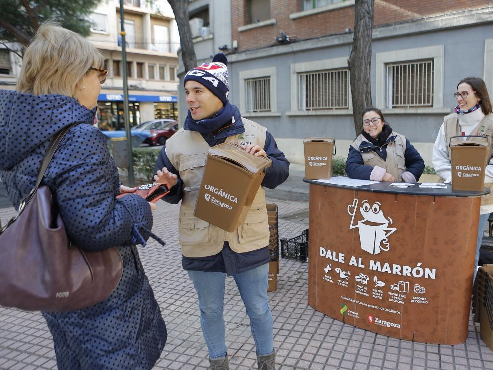 Un voluntario informa sobre el sistema de recogida en la calle de Tomás Bretón.