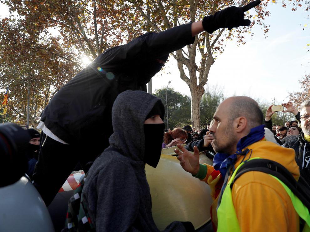 Un grupo de manifestantes trata de atravesar el cordón policial y otros tratan de impedirlo.