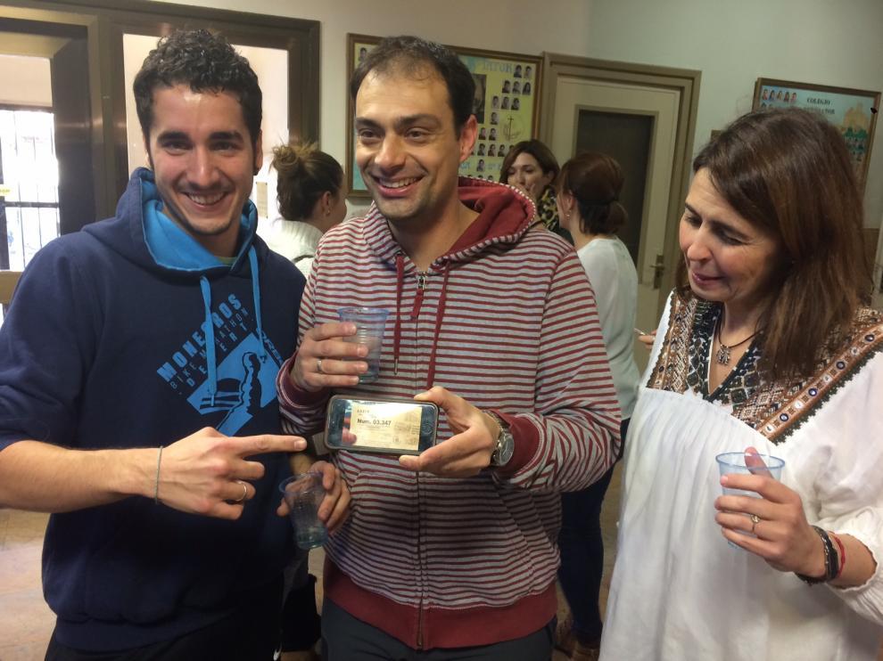 Joan Guardia enseña el móvil con una imagen de una de las participaciones agraciadas