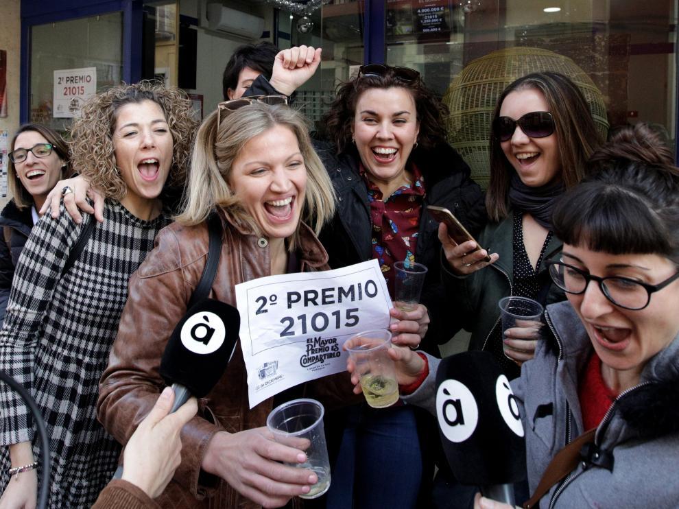 Varios premiados celebran este sábado un segundo premio en la administración de lotería alicantina de Pedreguer.