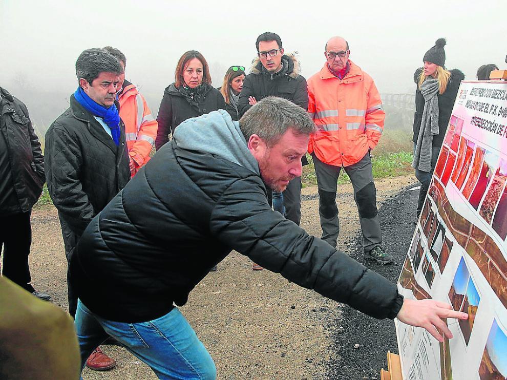 El consejero José Luis Soro señala una de la fotografías sobre la mejora de la carretera.