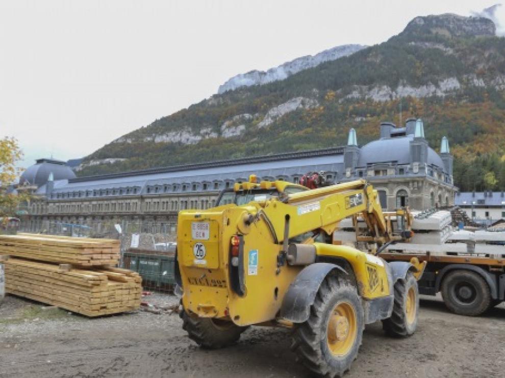Una grúa descarga vías y balasto para colocarla en la explanada de la estación de Canfranc