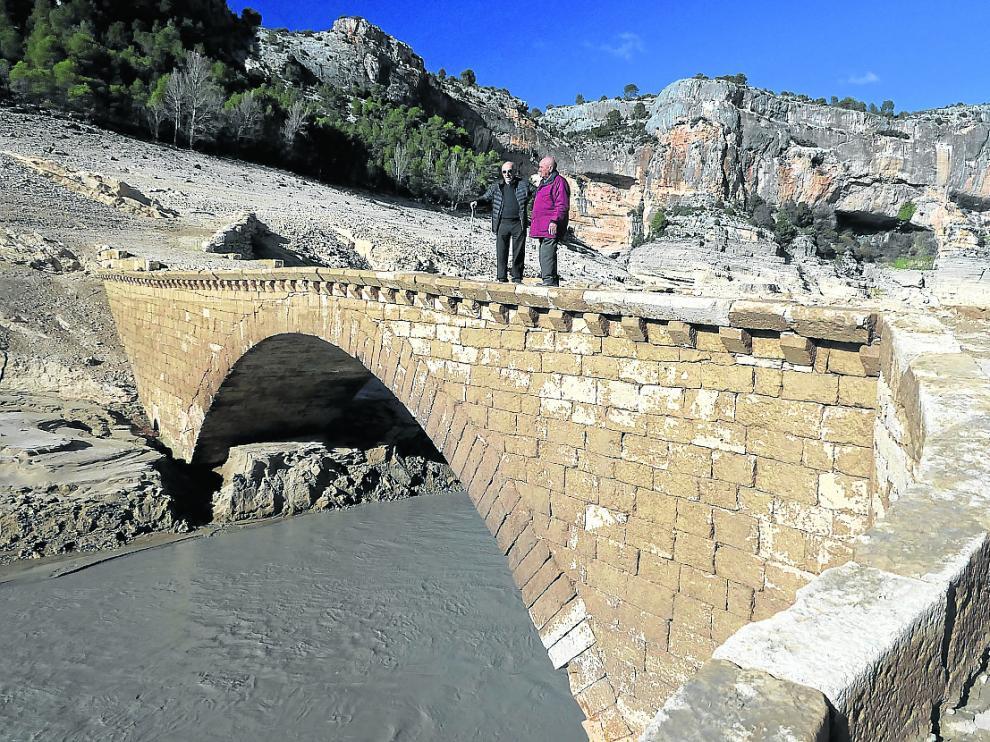 Perdiguer (izda.), antiguo vecino de Santolea, junto a un familiar en el puente aflorado.