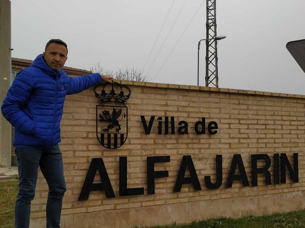 El alcalde de Alfajarín, junto a un letrero con la denominación de la localidad.