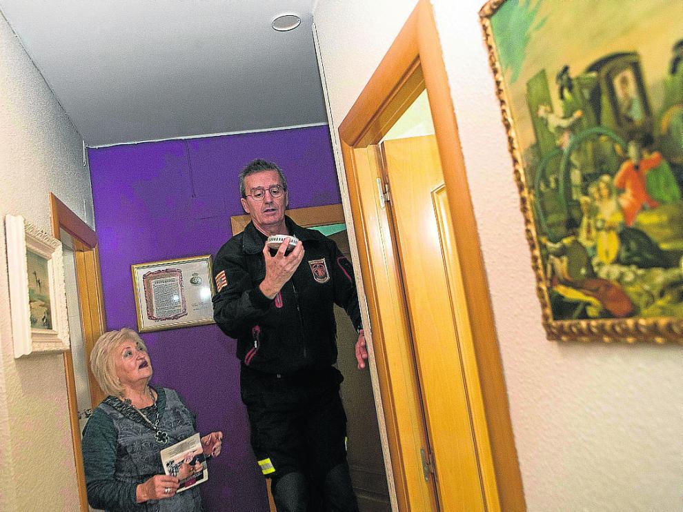 Carlos García, bombero del Museo de Fuego, explica a Soledad Lario el sistema de la alarma.