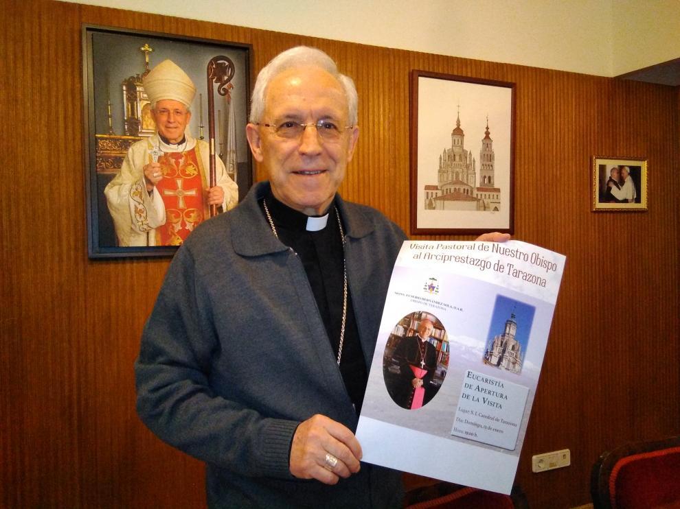 El obispo de Tarazona, Eusebio Hernández, junto al cartel que anuncia su Visita Pastoral.
