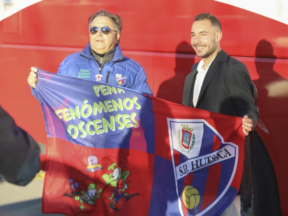 Ferreiro sujeta una bandera con el escudo de la SD Huesca, antes de partir hacia Leganés.