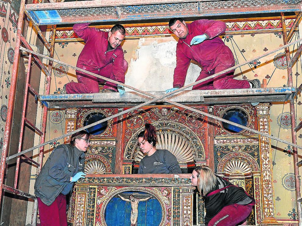 Restauradores y operarios ensamblan días atrás las 29 piezas del retablo.