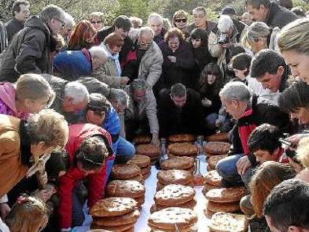 Los participantes en la romería buscan los langostos para ver el color que predice las cosechas