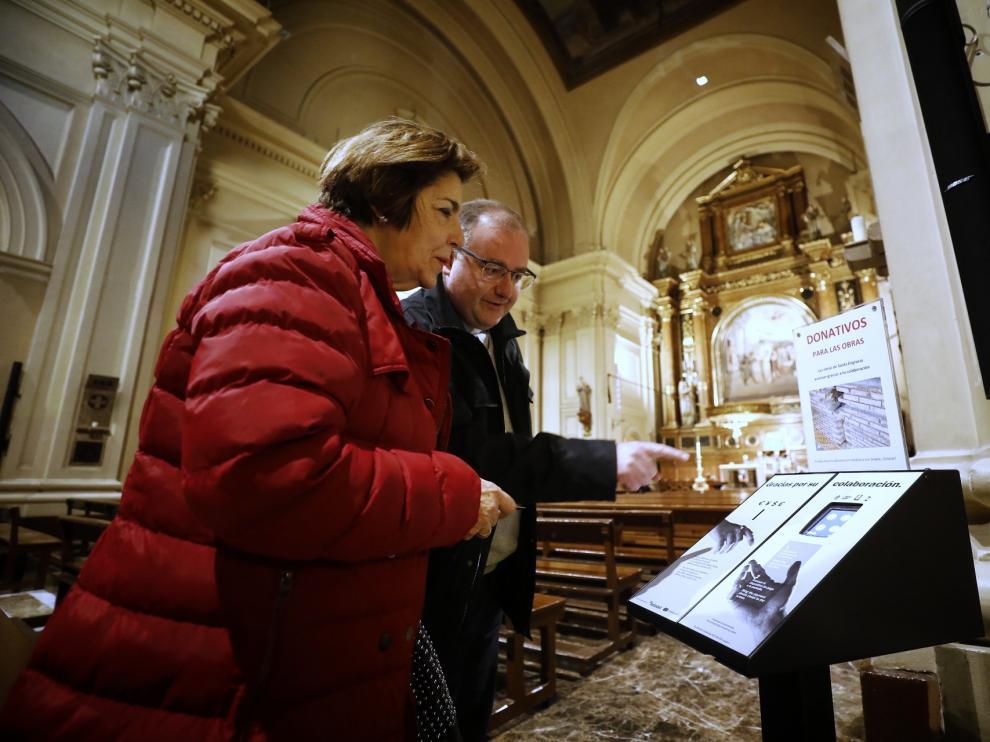 Santiago Aparicio, párroco de Santa Engracia, explica a una feligresa el funcionamiento del cepillo con datáfono.