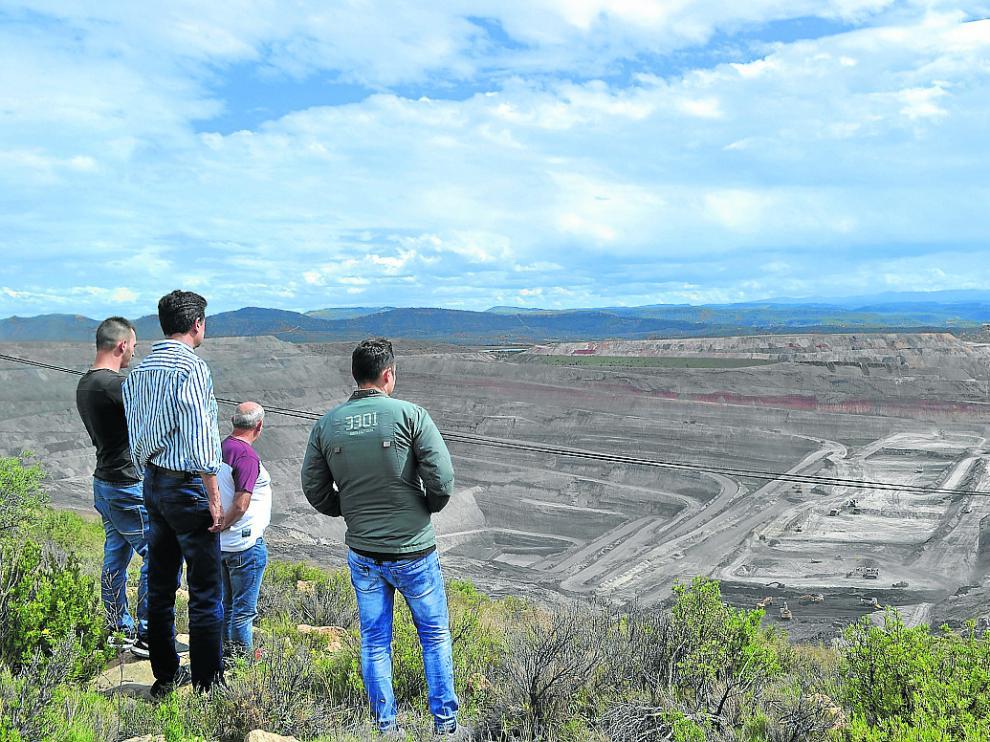 El alcalde de Ariño, Joaquín Noé, y un grupo de trabajadores observan la mina que se cierra