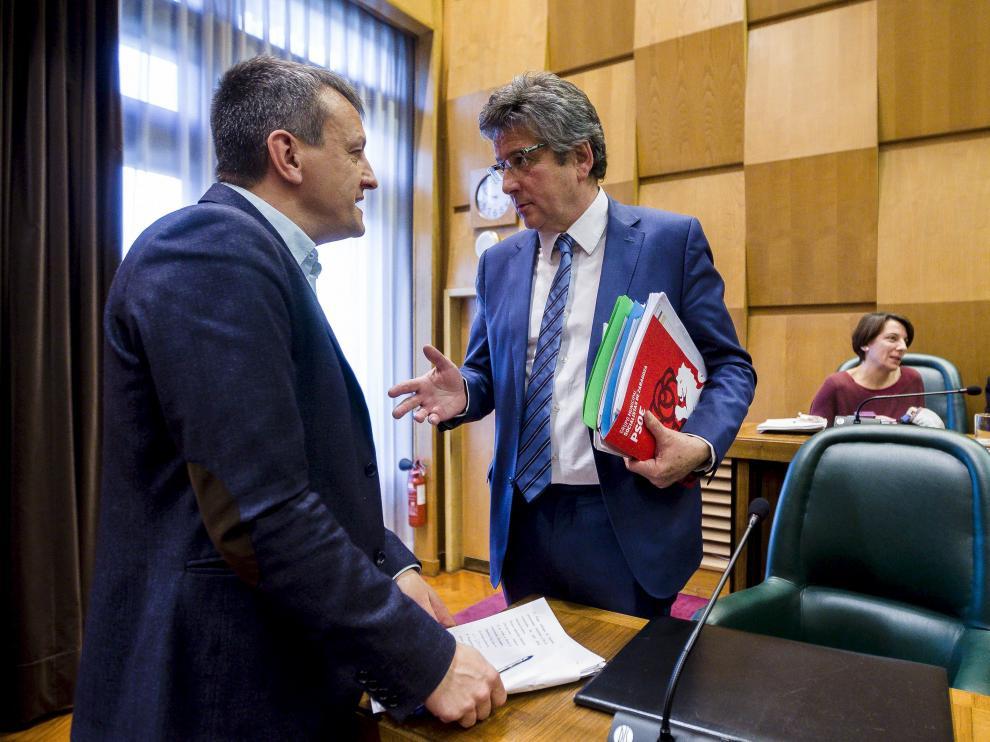 El concejal de Economía, Fernando Rivarés, conversa con el edil del PSOE Javier Trívez, en el salón de plenos del Ayuntamiento de Zaragoza.