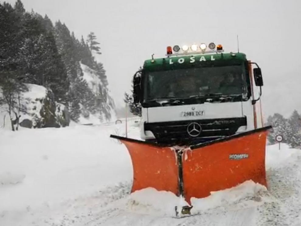 La máquina quitanieves despeja la carretera para dar paso a los vehículos que han abandonado el complejo turístico