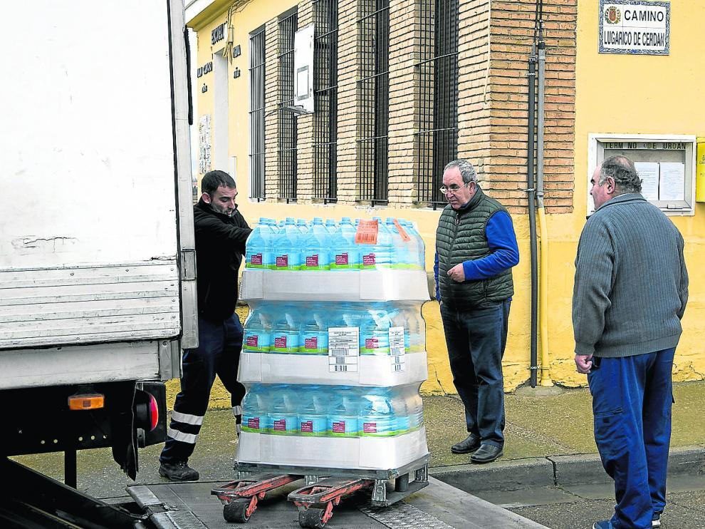 Dos vecinos de El Lugarico de Cerdán, Pepe Marqués y Ricardo Cobo, ayudaron a descargar este jueves las garrafas en las antiguas escuelas