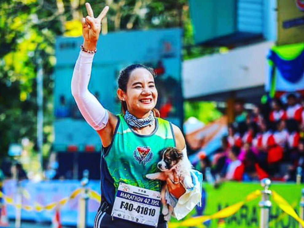 Khemjira Klongsanun con el cachorro en brazos corriendo la carrera en Tailandia.