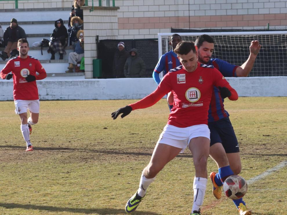 Un jugador del Calamocha pugna un balón ante la presión de un rival del Villanueva.