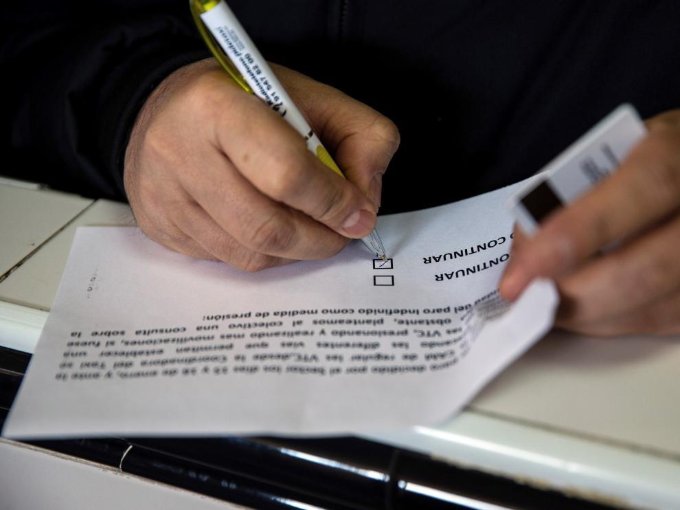 Un taxista escribe en una papeleta de la votación.