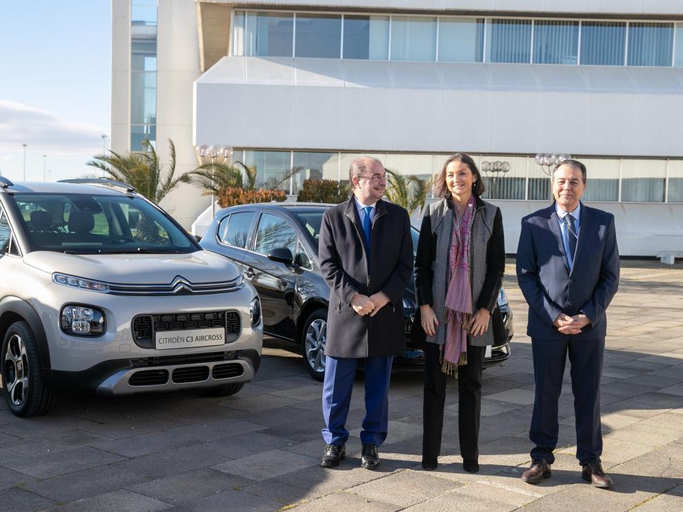 El presidente de Aragón, Javier Lambán, la ministra de Industria, Comercio y Turismo, Reyes Maroto, y el presidente de PSA Zaragoza, Juan Antonio Muñoz Codina posan frente a la factoría de Opel en Figueruelas.