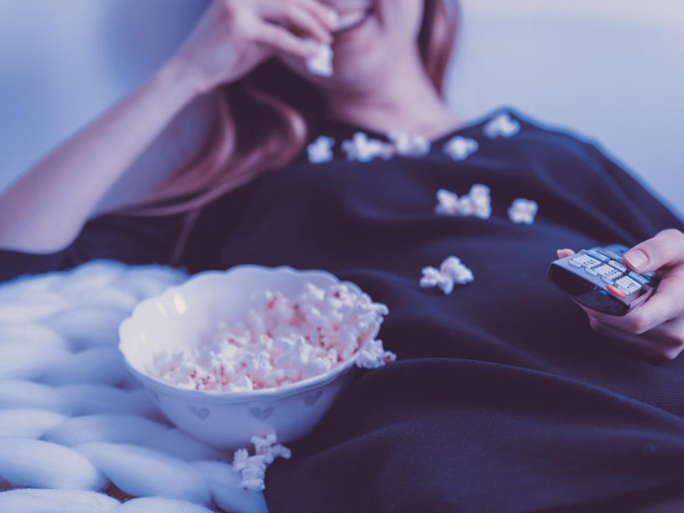Una mujer disfrutando de la programación de televisión