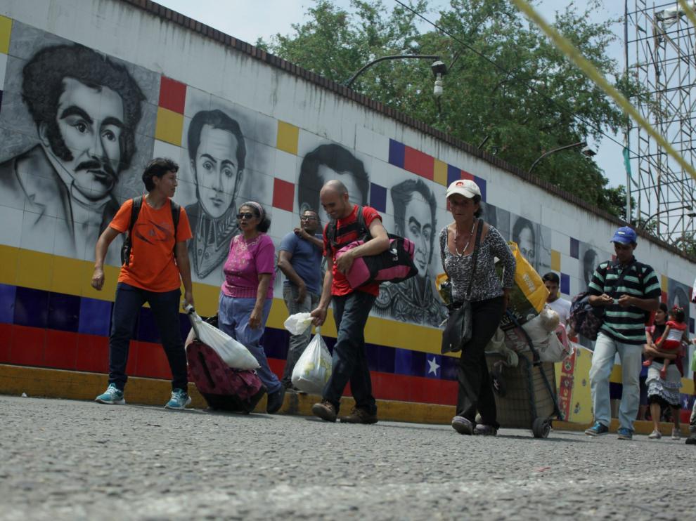 Varias personas cruzan la frontera entre Venezuela y Colombia.
