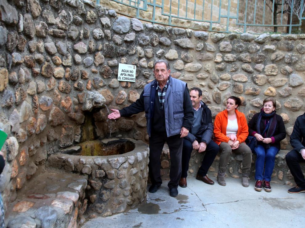 Vecinos de Plasencia del Monte junto a la fuente con el cartel 'Agua no apta para el consumo'