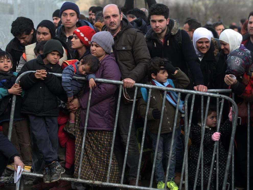 Migrantes y refugiados aguardan para cruzar la frontera entre Grecia y Macedonia, cerca de la aldea de Idomeni, en 2016