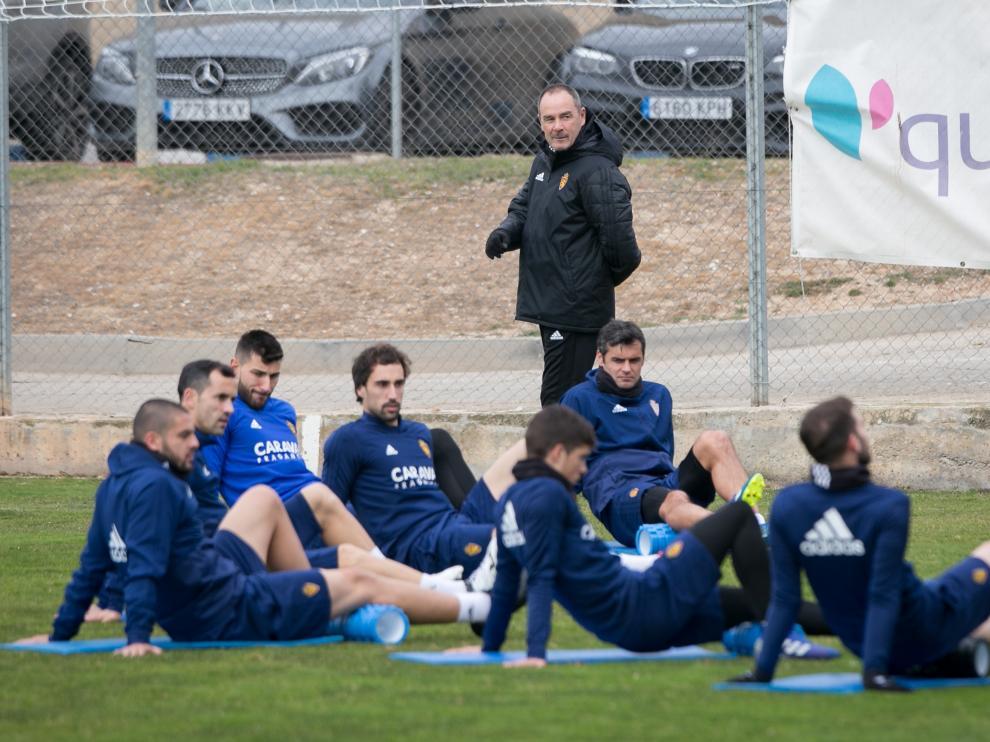 La plantilla del Zaragoza, bajo la mirada de Victor Fernández, estira en el entrenamiento de ayer en la Ciudad Deportiva.