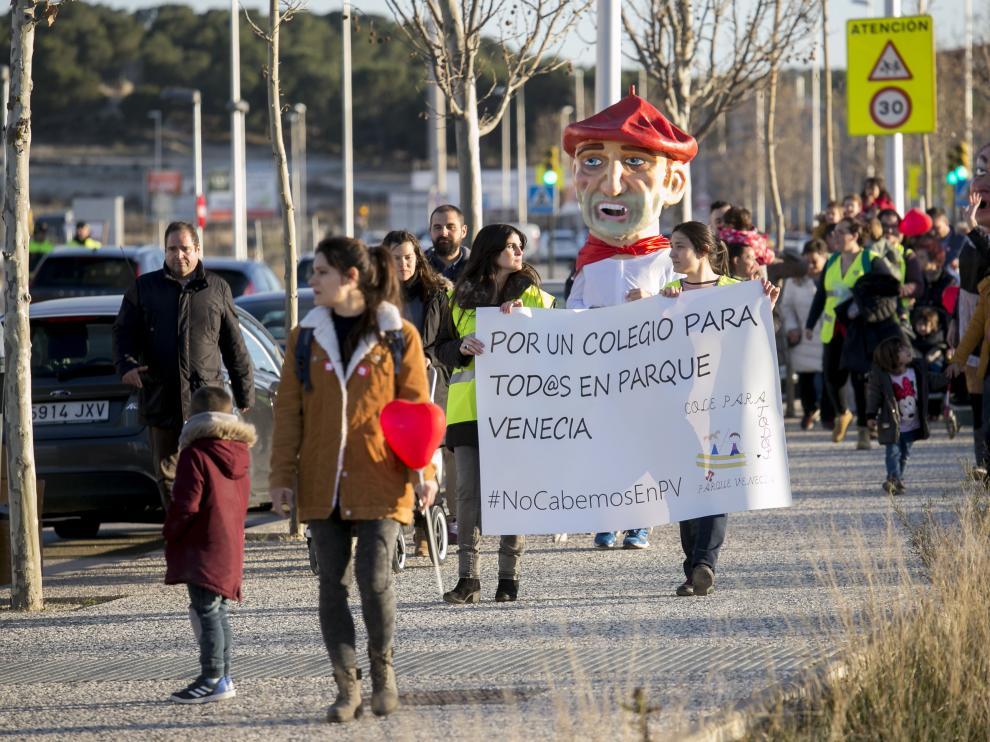 Las familias de Parque Venecia marchan hacia el solar donde se construirá el colegio.