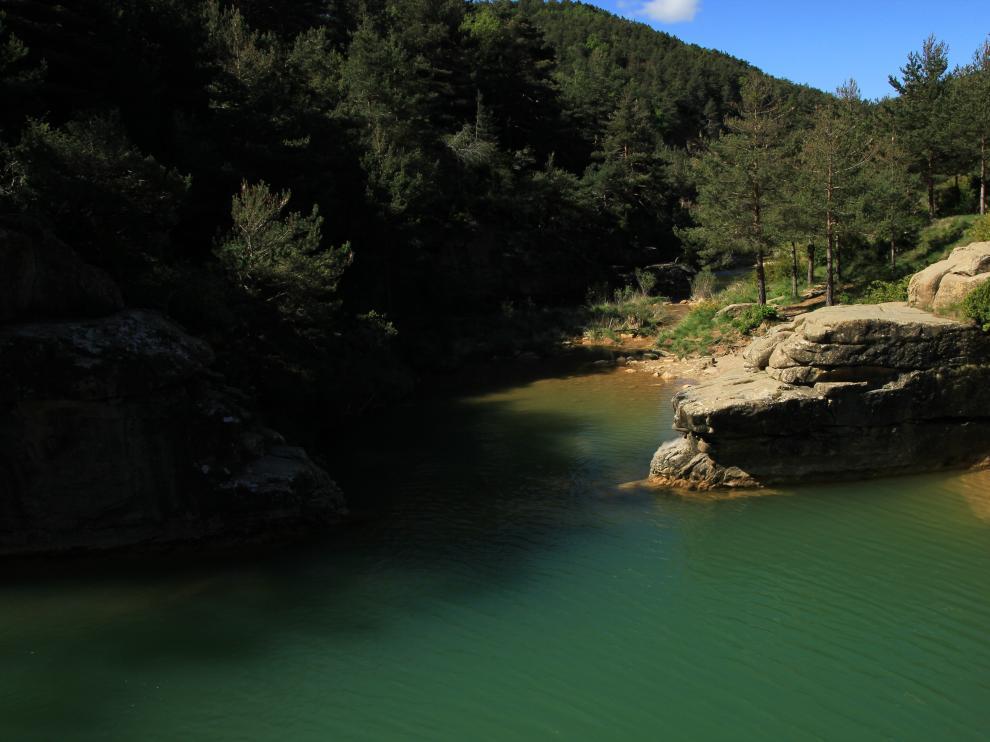 Las aguas verde esmeralda del pozo Pigalo, entre los cantiles de piedra y el bosque que lo rodean.