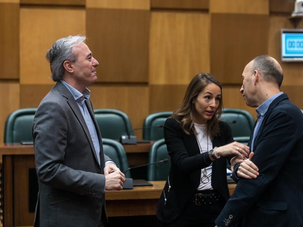 El portavoz del PP, Jorge Azcón, y la edil María Navarro, conversan este viernes con el portavoz de CHA, Carmelo Asensio.